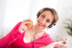 Cheerful young woman at home with tablet compuer Royalty Free Stock Images