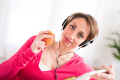 Cheerful young woman at home with tablet compuer Royalty Free Stock Photography