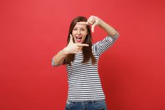Cheerful young woman keeping mouth wide open, looking surprised, making hands photo frame gesture isolated on bright red stock images