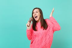 Cheerful young woman in knitted pink sweater dancing, spreading hands, holding sing song in microphone isolated on blue royalty free stock photos