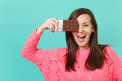 Cheerful young woman in knitted pink sweater holding in hand, covering eye with chocolate bar isolated on blue turquoise. Wall background, studio portrait royalty free stock photos