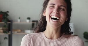 Cheerful young woman laughing looking at camera standing at home