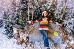 Cheerful young woman lie down with arms outstretched on a swing. With book and cup on it in a snow-covered park with spruce tree, wearing woolen sweater Royalty Free Stock Images