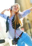 Cheerful young woman listening music in headphones in the city Royalty Free Stock Photo