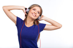Cheerful young woman listening music with headphones. royalty free stock images