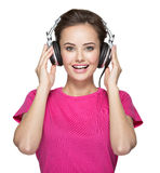 Cheerful young woman listening music with headphones Stock Photos