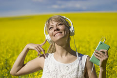 Cheerful young woman listening to music in a canola field.  Royalty Free Stock Image