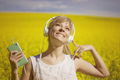 Cheerful young woman listening to music in a canola field. Cheerful young woman listening to music in a canola field Stock Photos