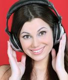 Cheerful young woman listening to music through headphones . Photo with copy space Royalty Free Stock Images