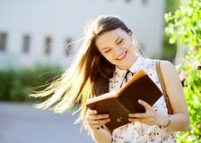 Cheerful young woman with long dark hair reads something. Summer sunny day, good weather. Woman has an excellent mood Royalty Free Stock Photos
