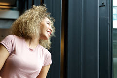 Cheerful young woman looking away out window. Portrait of cheerful young woman looking away out window Stock Photo