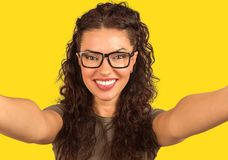 Cheerful young woman looking at camera and taking a selfie stock image