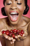 Cheerful young woman looking at cherry in her hands Royalty Free Stock Photos