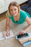 Cheerful young woman lying on floor using tablet to do her assig Stock Photography