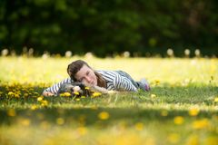 A cheerful, young woman lying on the grass with her pet. royalty free stock image