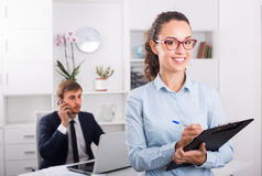 Cheerful young woman manager holding cardboard in office Royalty Free Stock Photos
