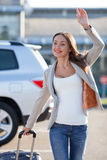 Cheerful young woman is meeting with someone at. Attractive girl is standing near her car and carrying a luggage. She is waving her arm and greeting with her Stock Images