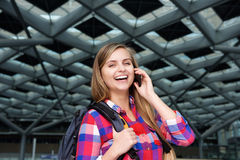 Cheerful young woman with mobile phone and backpack Stock Images