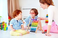 Cheerful young woman, mother playing games with kids at nursery room stock photos
