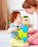 Cheerful young woman, mother playing games with kids at nursery room. Cheerful young woman, smilling mother playing games with baby boy at nursery room royalty free stock images