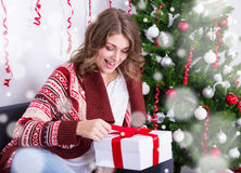 Cheerful young woman opening christmas gift near christmas tree Stock Image