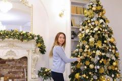 Joyful girl decorates Christmas tree and prepares for holidays o Stock Images