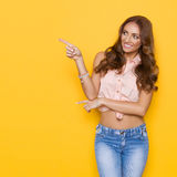 Cheerful Young Woman In Pink Pastel Shirt Pointing Stock Photography
