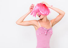 Cheerful young woman in pink wig and dancing on white background Royalty Free Stock Photos