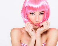 Cheerful young woman in pink wig posing on white background Stock Images