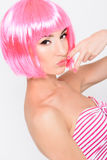 Cheerful young woman in pink wig posing on white background Royalty Free Stock Image