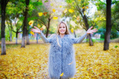 Cheerful young woman playing with autumn leaves Stock Photography