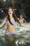 Cheerful Young Woman Playing With Friend In Water Stock Photos