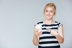 Cheerful young woman pointing on cup for coffe to go Royalty Free Stock Photo