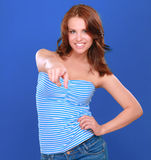 Cheerful young woman pointing finger at camera isolated on the blue background Royalty Free Stock Images