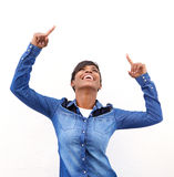 Cheerful young woman pointing fingers up. Portrait of a cheerful young woman pointing fingers up to copy space on white background Royalty Free Stock Photography