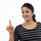 Cheerful young woman pointing on a virtual screen Stock Photo