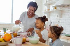 Cheerful young woman pouring down milk into bowl. Ready to eat. Kind dark-skinned mommy expressing positivity while preparing breakfast with pleasure stock photography