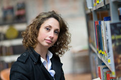 Cheerful young woman in public library Royalty Free Stock Image