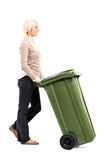 Cheerful young woman pushing a garbage can. Isolated on white background stock photos