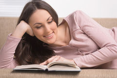 Cheerful young woman reading a book while Stock Images