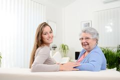 Cheerful young woman reading a book for old senior woman at home. Cheerful young women reading book for old senior women at home Royalty Free Stock Image