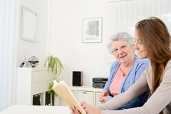 Cheerful young woman reading a book for old senior woman at home. Cheerful young women reading book for old senior women at home Stock Images