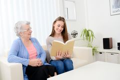 Cheerful young woman reading a book for old senior woman at home. Cheerful young women reading book for old senior women at home Royalty Free Stock Photography