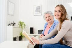 Cheerful young woman reading a book for old senior woman at home. Cheerful young women reading book for old senior women at home Stock Photo