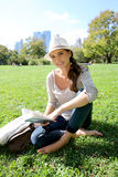 Cheerful young woman reading guide in central park Stock Photography