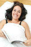 Cheerful young woman reading in her bed Royalty Free Stock Photography