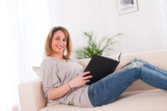 Cheerful young woman reading at home. Cheerful young woman at home reading on her sofa Royalty Free Stock Photography