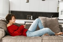 Cheerful young woman relaxing at home stock photos