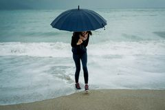 Cheerful Young woman  runs from the wave with an umbrella in fro. Nt sea in winter or autumn Stock Photography