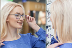 Cheerful young woman is selecting new spectacles Stock Photos